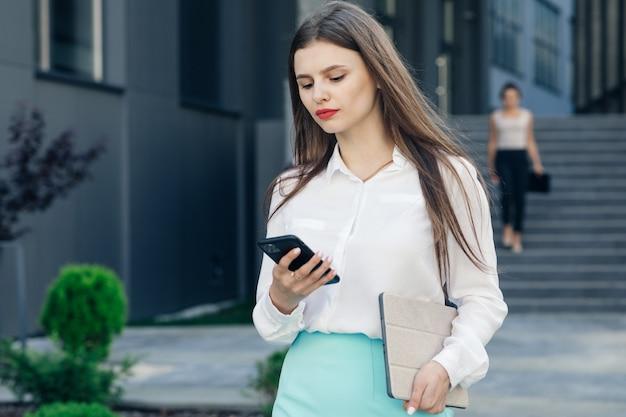 彼女の電話を屋外で使うスタイリッシュな実業家。建物の前で彼女のスマートフォンを使用してメッセージを読んで長い髪の美しい女性。