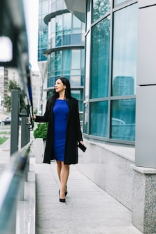 Stylish businesswoman walking outside building