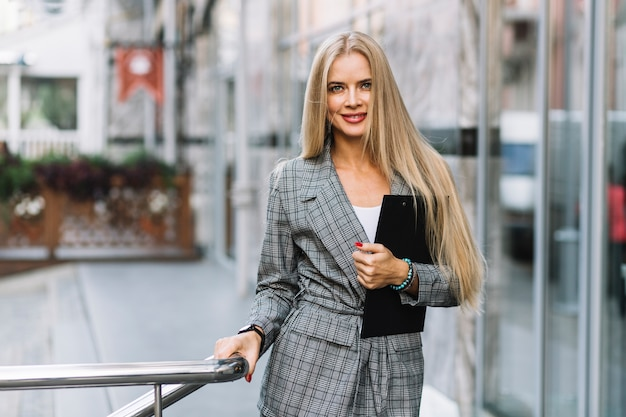 Stylish businesswoman with clipboard in city