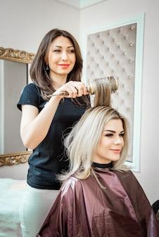 あなたが信頼できる専門家によるスタイリッシュ。美容院の背景にヘアドライヤーで彼女のクライアントの髪をしている若い美しい美容師の鏡像