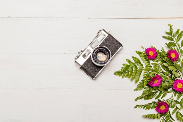 Stylish camera and pink flowers with green leaves