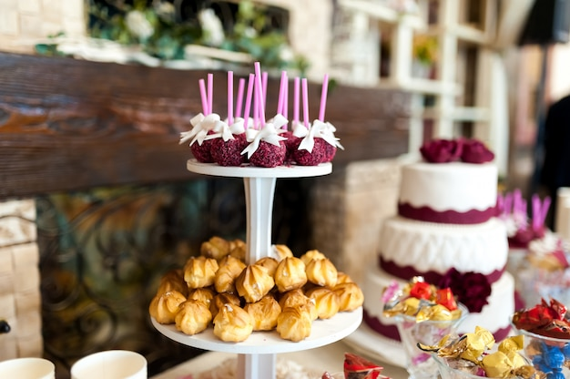 Stylish candy bar with cakes, candies, sweet cookies, cake pops. delicious assortment for wedding banquet. candy bar inside restaurant.