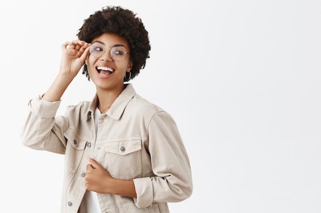 メガネとベージュのシャツを着たスタイリッシュなのんきで自信に満ちた女性の浅黒い肌の女性、服に触れて楽しそうに笑う