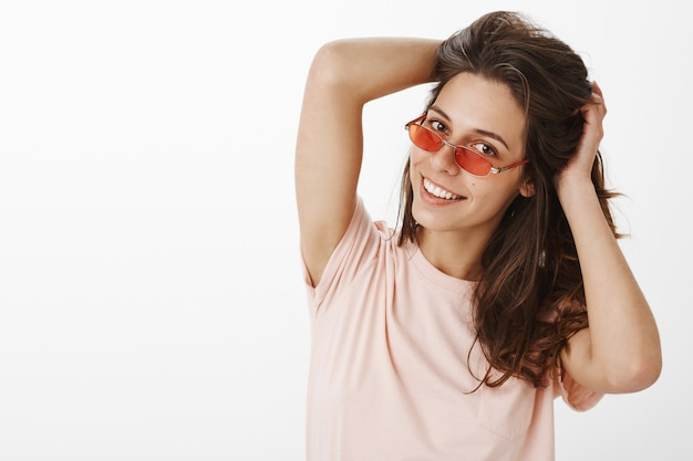 Stylish carefree girl with sunglasses posing against the white wall