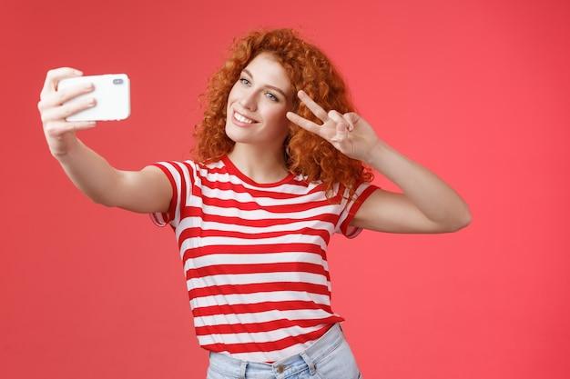 Стильная беззаботная красивая рыжая кудрявая женщина наслаждается летними каникулами, шоу победа, жест мира, наклон головы, милый, запись видео, удержание смартфона, принятие селфи на красном фоне. копировать пространство