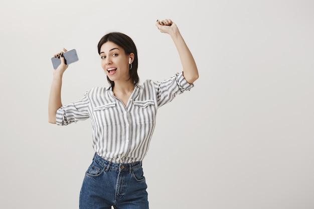 Elegante donna spensierata ascoltando musica in auricolari wireless, ballando con lo smartphone in mano