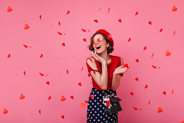 バレンタインデーにポーズをとるスタイリッシュな屈託のない女性。赤い紙吹雪の下に立っているベレー帽の魅力的な巻き毛の女の子を笑っています。