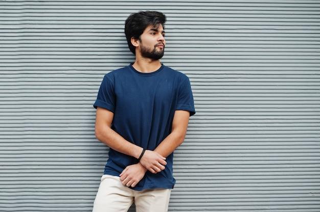 Стильный случайный индийский мужчина в синей футболке позирует на серой стене.