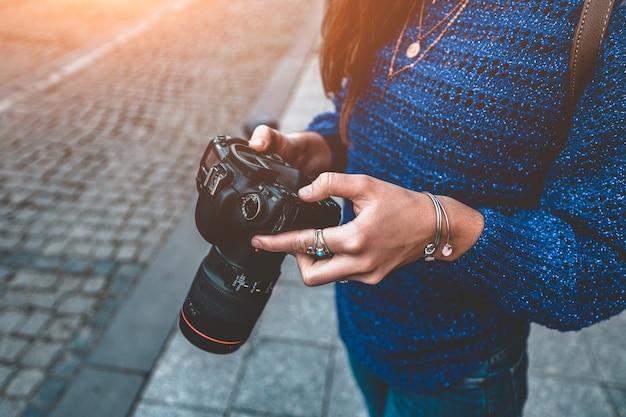 Стильная случайная женщина фотографа путешественника фотографируя с цифровой камерой dslr и объективом slr во время гулять вокруг европейского города