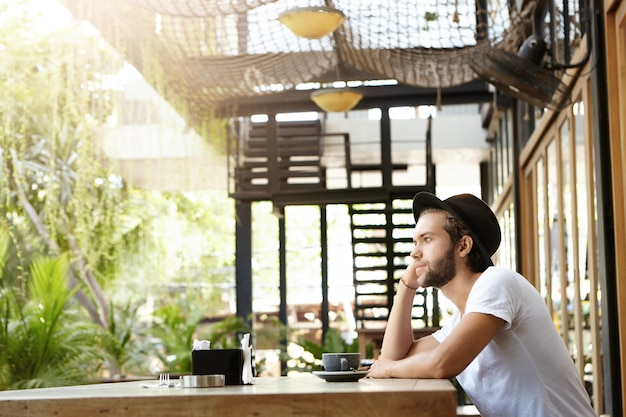 Stylish caucasian bearded student in headwear drinking cappuccino alone at modern outdoor coffee shop on sunny day, waiting for his girlfriend to join him