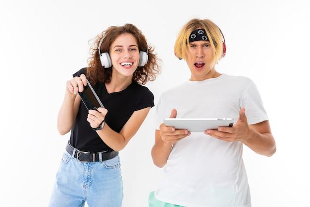 Стильный кавказский блондин и молодая женщина показывают планшет и слушают музыку, изолированные на белом фоне