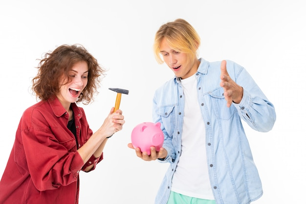 Stylish caucasian blonde man and young woman holds a moneybox isolated on white background