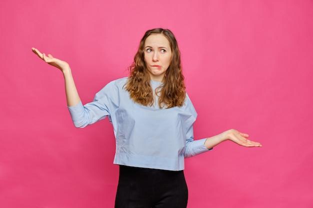 淡いブルーのtシャツを着たスタイリッシュな白人少女は、ピンクの背景に悔しさのある手の抽象的なスケールを示しています。