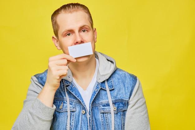 Стильный мужчина кавказской в джинсах на желтом фоне держит белую карточку на уровне рта копией пространства.