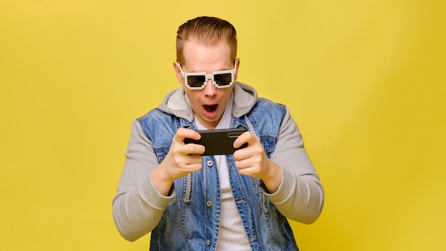 Stylish caucasian man in a jeans on a yellow background with 8 bit glasses. play with surprise on a smartphone.