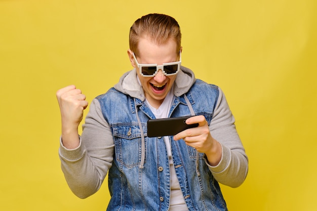 Stylish caucasian man in a jeans on a yellow background with 8 bit glasses. with excitement, play on your smartphone and win.