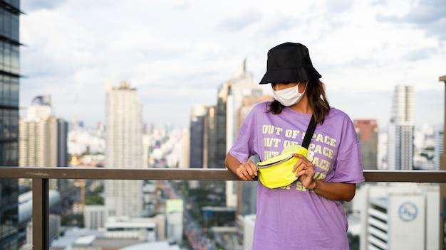 Стильная кавказская женщина в модной панаме и неоновой сумке на талии на крыше в бангкоке