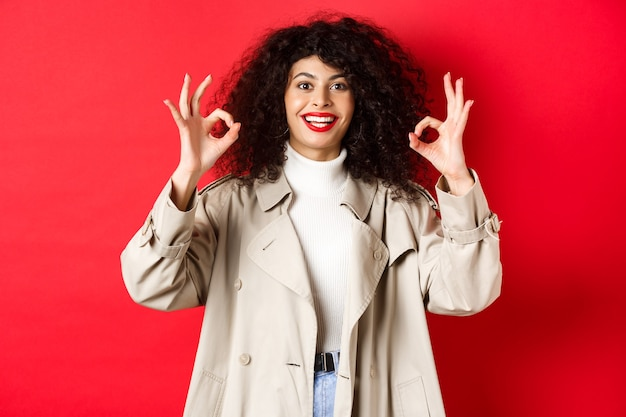 Stylish caucasian woman in trench coat showing okay gesture and smiling satisfied, recommending company, standing on red background.