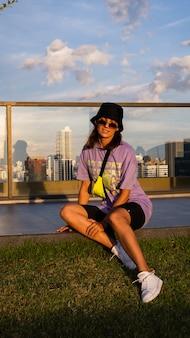 Elegante donna caucasica in panama alla moda e borsa al neon in vita sul tetto a bangkok