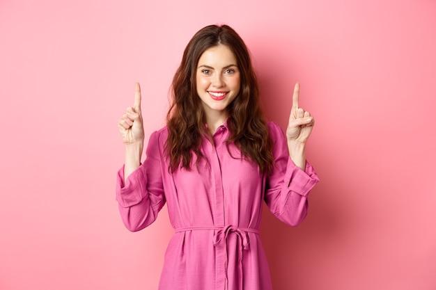 곱슬 머리와 가벼운 유행 드레스, 세련 된 백인 여자, 분홍색 벽에 서있는 복사본 공간을 보여주는 로고에서 손가락을 가리키는 기쁘게 미소.