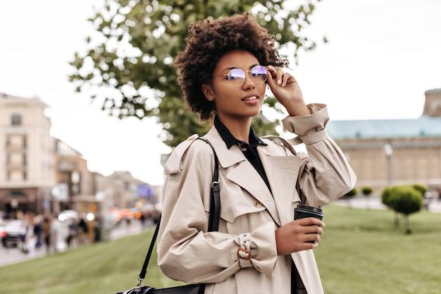 베이지색 트렌치 코트를 입은 세련된 갈색 머리 여성은 안경을 쓰고 커피 컵을 들고 야외에서 포즈를 취합니다.