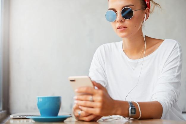 日陰のスタイリッシュな魅力的な女性、スマートフォンに接続されたモダンなイヤホンを使用、ソーシャルネットワークで興味深いビデオを視聴、またはオーディオトラックを聴く、コーヒーショップで無料のインターネット接続を使用する