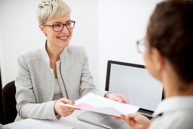 Стильная очаровательная счастливая женщина средних лет с короткими волосами получает все запрошенные документы для банковского кредита в офисе от работницы.