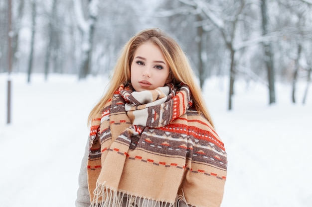 Stylish charming young woman blonde in a vintage woolen scarf with a beautiful pattern in a gray coat