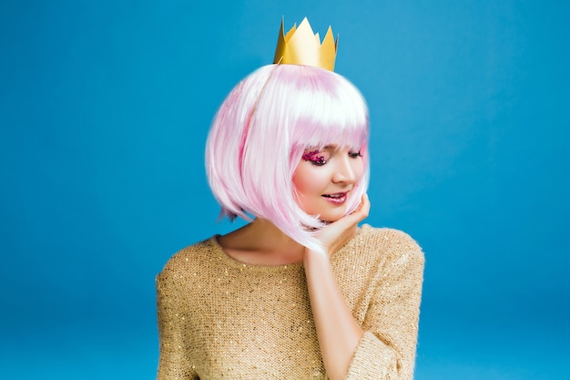Stylish charming young woman with cut pink hair. golden sweater, crown on head, smiling with closed eyes, true emotions, party time, makeup with pink tinsels.