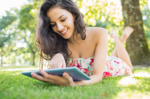 Stylish cheerful brunette lying on a lawn using tablet