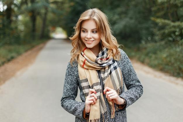 빈티지 베이지 체크 무늬 스카프에 세련된 회색 코트에 귀여운 미소로 세련된 쾌활한 유럽 젊은 여성이 따뜻한 봄날 야외에서 산책