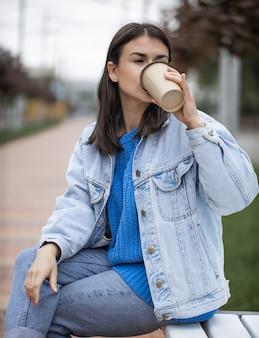 カジュアルなスタイルのスタイリッシュな陽気な女の子は、散歩でテイクアウトコーヒーを楽しんでいます。
