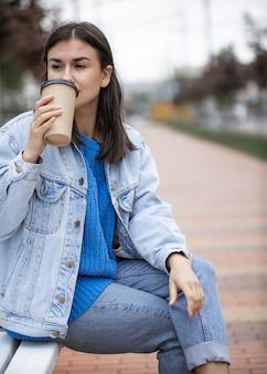 캐주얼 스타일의 세련된 명랑 소녀는 산책에 테이크 아웃 커피를 즐깁니다.