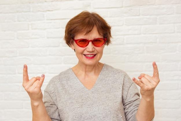 スタイリッシュな寒さとトレンディな赤いサングラスの素晴らしい年配の女性が再び若く感じるロックンロールのジェスチャーを示しています