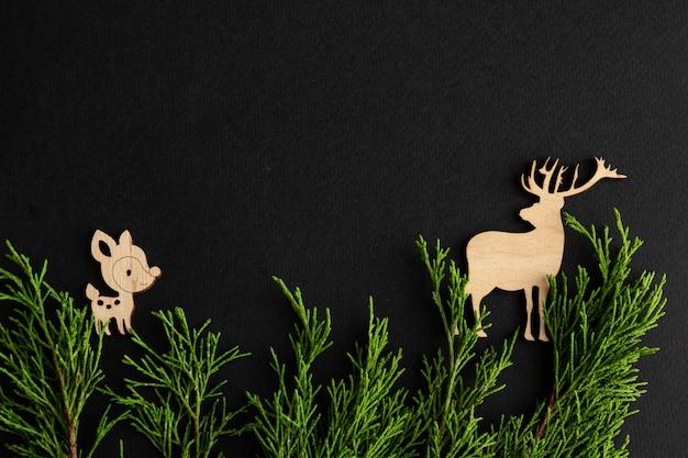Стильная новогодняя композиция на черном фоне деревянные оленьи еловые ветки копией пространства