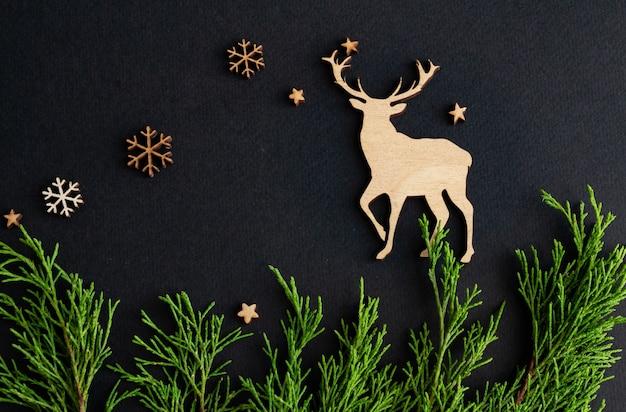 Стильная новогодняя композиция на черном фоне деревянные олени снежинки еловые ветки копией пространства