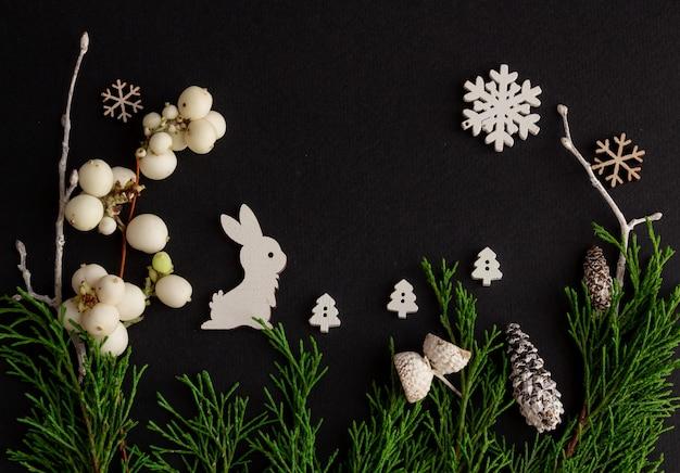 Стильная новогодняя композиция на черном фоне деревянные заяц снежинки копией пространства