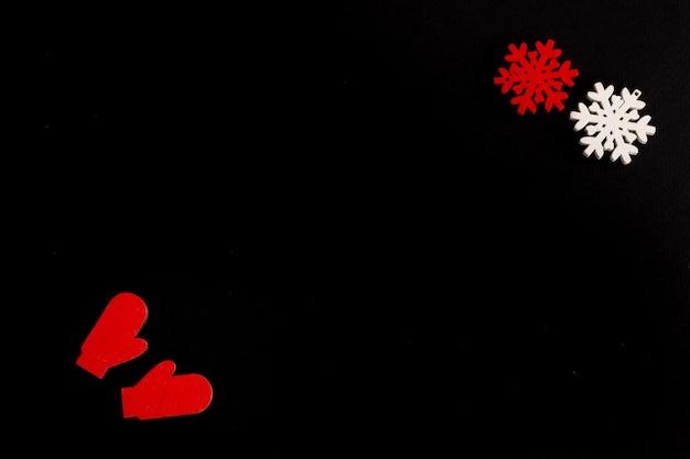 Стильная новогодняя композиция на черном фоне из деревянных снежинок и варежек копирует пространство