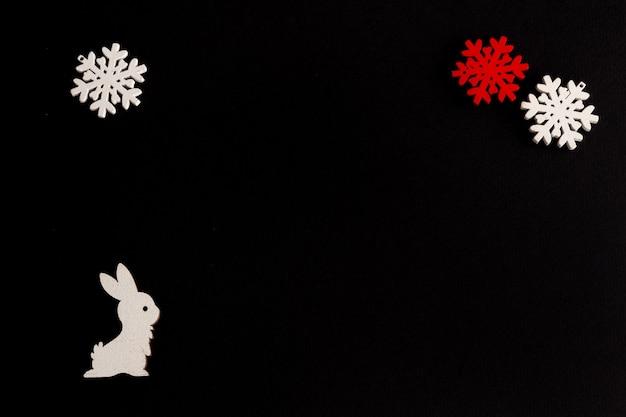 Стильная новогодняя композиция на черном фоне деревянный беляк и снежинки копируют пространство