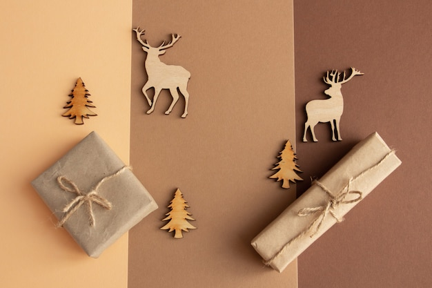 Стильная новогодняя композиция на коричнево-бежевом фоне, подарки и деревянные фигурки копируют пространство