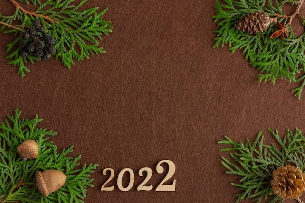 Стильная новогодняя композиция из еловых веток на коричневом фетровом фоне копией пространства
