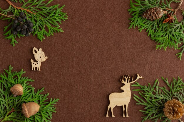 Стильная новогодняя композиция из еловых веток с деревянными фигурками оленей на фоне коричневого фетра