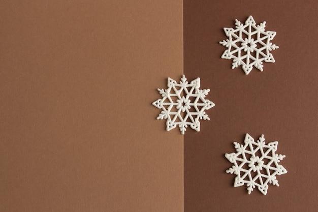 Стильная новогодняя композиция из белых снежинок на коричнево-бежевом фоне с копией пространства