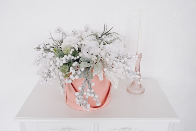Stylish christmas decoration, bouquet of roses alongside an ornamental candle