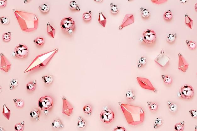 Стильная новогодняя рамка с блестящими шарами и золотыми кристаллами на пастельно-розовом фоне. плоская планировка, вид сверху