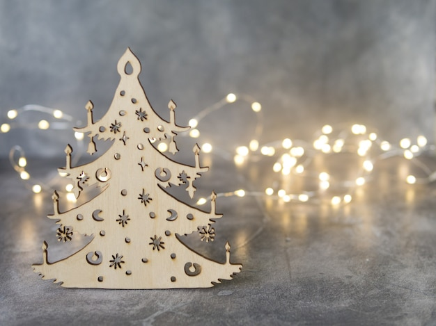 Stylish christmas handmade tree made of wood on gray background with glowing lights.