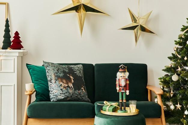 Стильный интерьер рождественской гостиной с зеленым диваном, белым камином, елкой и венком, звездами, подарками и украшениями. время для семьи. шаблон.