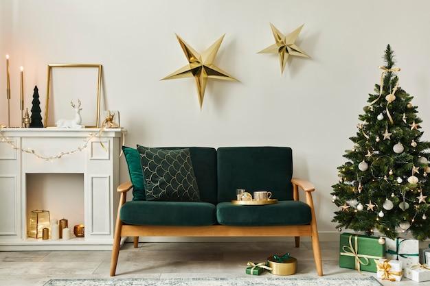 緑のソファ、白い煙突、クリスマスツリーと花輪、星、ギフト、装飾が施されたスタイリッシュなクリスマスのリビングルームのインテリア。家族の時間。レンプレート。