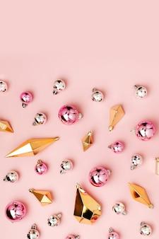 Стильный рождественский узор с блестящими шарами и золотыми кристаллами на пастельно-розовом фоне. плоская планировка, вид сверху