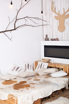 Stylish christmas scandinavian minimalistic interior with an elegant sofa. comfort home. modern country house interior with wooden bed, firewood, fireplace. christmas decor in a room idoor.